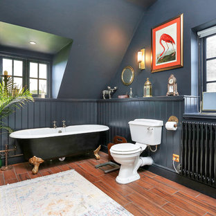 Inspiration for a traditional bathroom in Cambridgeshire with raised-panel cabinets, dark wood cabinets, a claw-foot bath, a two-piece toilet, black walls, medium hardwood flooring, a vessel sink, brown floors and white worktops.