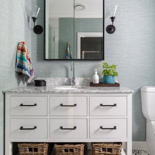 Foto de cuarto de baño principal y papel pintado, tradicional renovado, pequeño, papel pintado, con encimeras grises, papel pintado, armarios tipo mueble, puertas de armario blancas, sanitario de dos piezas, paredes azules, suelo con mosaicos de baldosas, lavabo bajoencimera y suelo multicolor