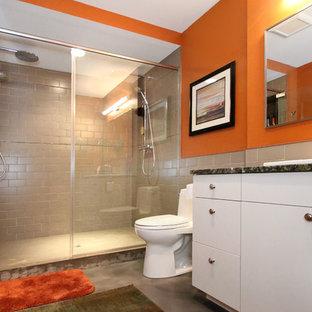 中サイズのコンテンポラリースタイルのおしゃれな浴室 (オーバーカウンターシンク、フラットパネル扉のキャビネット、白いキャビネット、御影石の洗面台、オープン型シャワー、一体型トイレ、グレーのタイル、磁器タイル、オレンジの壁、コンクリートの床、茶色い床、開き戸のシャワー、マルチカラーの洗面カウンター) の写真