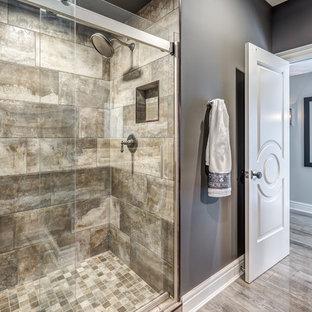 Großes Klassisches Duschbad mit verzierten Schränken, hellbraunen Holzschränken, Duschnische, grauer Wandfarbe, Vinylboden, integriertem Waschbecken, Granit-Waschbecken/Waschtisch, braunem Boden, Schiebetür-Duschabtrennung und beiger Waschtischplatte in Sonstige