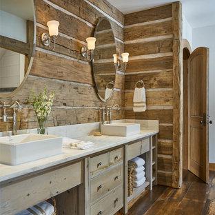 Ejemplo de cuarto de baño rústico con armarios con paneles lisos, puertas de armario de madera clara, paredes blancas, suelo de madera en tonos medios, lavabo sobreencimera, suelo marrón y encimeras blancas