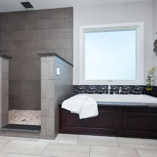 Bathroom - mid-sized modern master gray tile and porcelain tile porcelain floor and gray floor bathroom idea in Other with recessed-panel cabinets, dark wood cabinets, gray walls and granite countertops
