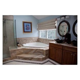 Foto på ett stort vintage en-suite badrum, med ett fristående handfat, luckor med infälld panel, skåp i mellenmörkt trä, bänkskiva i onyx, ett hörnbadkar, en hörndusch, en toalettstol med separat cisternkåpa, beige kakel, stenkakel, blå väggar och marmorgolv