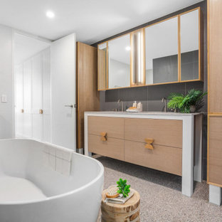This is an example of a contemporary master bathroom in Central Coast with flat-panel cabinets, medium wood cabinets, a freestanding tub, gray tile, multi-coloured benchtops, a double vanity and a built-in vanity.