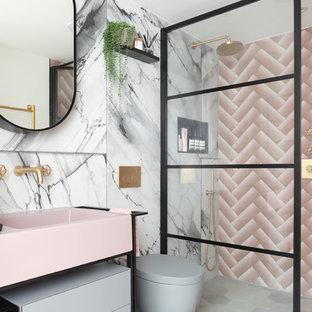Mittelgroßes Modernes Badezimmer En Suite mit verzierten Schränken, offener Dusche, Wandtoilette, rosafarbenen Fliesen, Metrofliesen, rosa Wandfarbe, Zementfliesen, Mineralwerkstoff-Waschtisch, grauem Boden, Falttür-Duschabtrennung und rosa Waschtischplatte in London