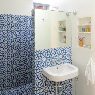 Cette photo montre une salle d'eau tendance de taille moyenne avec un carrelage bleu, une douche ouverte, carrelage en mosaïque, un mur blanc, un sol en carrelage de terre cuite, un plan de toilette en surface solide, aucune cabine, un lavabo suspendu et un sol bleu.