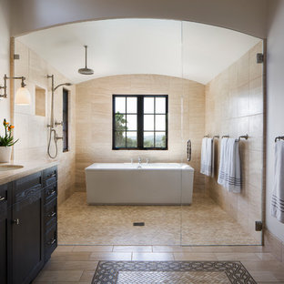 Photo of a large mediterranean bathroom in Santa Barbara with dark wood cabinets, a freestanding bath, beige tiles, travertine tiles, ceramic flooring, a submerged sink, beige floors, a hinged door, recessed-panel cabinets, white walls and brown worktops.