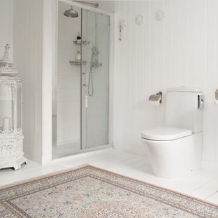 Photo of a romantic bathroom in Other with white cabinets, an alcove shower, a two-piece toilet, white tiles, white walls, painted wood flooring, white floors, a sliding door, white worktops, a freestanding vanity unit and tongue and groove walls.