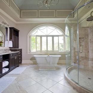 ボルチモアの巨大なヴィクトリアン調のおしゃれなマスターバスルーム (アンダーカウンター洗面器、落し込みパネル扉のキャビネット、濃色木目調キャビネット、置き型浴槽、ベージュのタイル、磁器タイル、グレーの壁、トラバーチンの床、御影石の洗面台、アルコーブ型シャワー) の写真