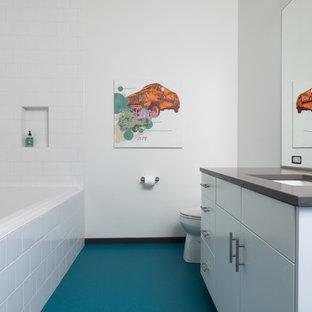 Ispirazione per una grande stanza da bagno per bambini minimalista con lavabo sottopiano, ante lisce, ante bianche, vasca da incasso, doccia ad angolo, WC monopezzo, piastrelle bianche, piastrelle in ceramica, pareti bianche, pavimento in linoleum e pavimento blu