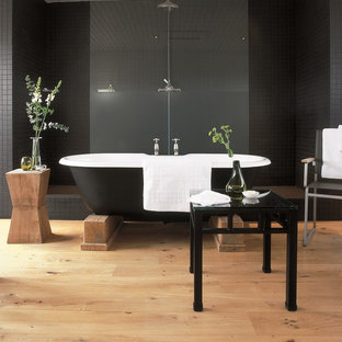 Inspiration for a large eclectic master black tile and ceramic tile light wood floor bathroom remodel in London with black walls