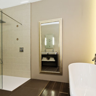 Example of a large trendy master multicolored tile and porcelain tile porcelain floor bathroom design in Dublin with furniture-like cabinets, a wall-mount toilet, beige walls, a console sink, granite countertops and dark wood cabinets