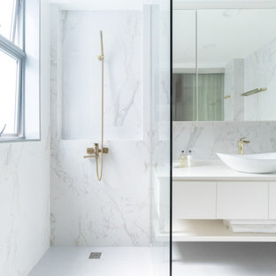 Immagine di una stanza da bagno minimal con ante lisce, ante bianche, piastrelle bianche, lastra di pietra, lavabo a bacinella, pavimento bianco e top bianco