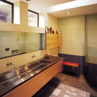 Свежая идея для дизайна: большая ванная комната в современном стиле с раковиной с несколькими смесителями, плоскими фасадами, светлыми деревянными фасадами, столешницей из нержавеющей стали, открытым душем, зеленой плиткой, стеклянной плиткой, желтыми стенами и полом из сланца - отличное фото интерьера