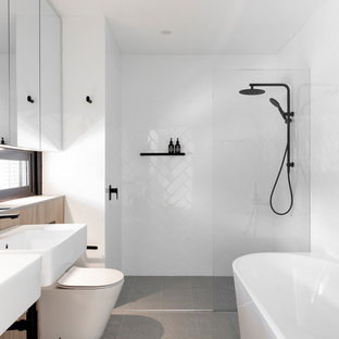This is an example of a contemporary master bathroom in Sydney with white tile, white walls, a wall-mount sink, grey floor, an open shower, a freestanding tub, an alcove shower and a one-piece toilet.