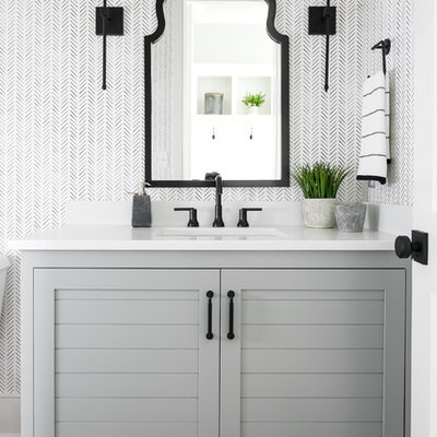 Inspiration for a transitional dark wood floor and brown floor bathroom remodel in Louisville with furniture-like cabinets, gray cabinets, multicolored walls, an undermount sink and white countertops