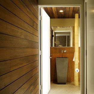Idee per una stanza da bagno design di medie dimensioni con lavabo a colonna, piastrelle di vetro, pareti arancioni e pavimento in cemento