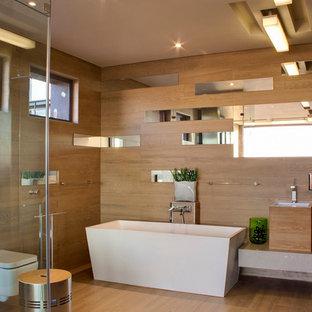 На фото: ванная комната в современном стиле с подвесной раковиной, отдельно стоящей ванной, инсталляцией, зеркальной плиткой, бежевыми стенами и паркетным полом среднего тона с