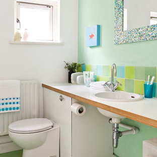Coastal green tile and ceramic tile ceramic floor and green floor bathroom photo in Other with a drop-in sink, wood countertops, a two-piece toilet, green walls and white countertops