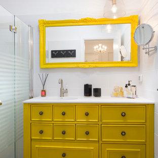 Stilmix Badezimmer mit verzierten Schränken, gelben Schränken, bodengleicher Dusche, weißen Fliesen und weißer Wandfarbe in Sonstige