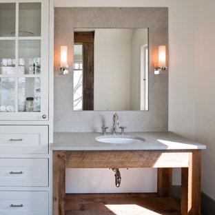 Foto di una stanza da bagno stile marinaro con lavabo sottopiano, pareti bianche, ante con finitura invecchiata, nessun'anta e top grigio