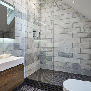 Photo of a small contemporary wet room in London with flat-panel cabinets, brown cabinets, a one-piece toilet, marble tiles, grey walls, black floors and an open shower.