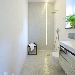 Foto di una stanza da bagno industriale con pareti bianche, pavimento con piastrelle a mosaico, ante di vetro, ante in legno scuro, doccia ad angolo, WC sospeso, piastrelle bianche, piastrelle di vetro, lavabo integrato e top in vetro