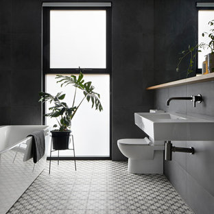 Design ideas for a large modern master bathroom in Melbourne with flat-panel cabinets, light wood cabinets, a freestanding tub, an open shower, a one-piece toilet, gray tile, porcelain tile, a wall-mount sink, black walls, cement tiles and grey floor.