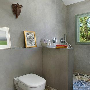 Imagen de cuarto de baño bohemio con ducha abierta, sanitario de pared y ducha abierta