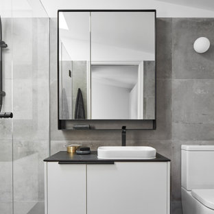 This is an example of a mid-sized contemporary 3/4 bathroom in Melbourne with flat-panel cabinets, a one-piece toilet, gray tile, ceramic tile, grey walls, ceramic floors, a vessel sink, solid surface benchtops, grey floor, a hinged shower door, black benchtops, a single vanity, a floating vanity, vaulted and white cabinets.