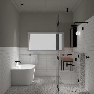 Стильный дизайн: детская ванная комната в современном стиле с черными фасадами, отдельно стоящей ванной, угловым душем, унитазом-моноблоком, белой плиткой, керамической плиткой, белыми стенами, полом из терраццо, раковиной с несколькими смесителями, столешницей из бетона, бежевым полом, душем с распашными дверями, оранжевой столешницей, тумбой под одну раковину и напольной тумбой - последний тренд