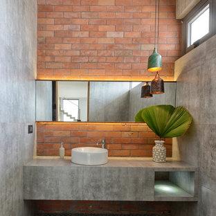Industriell inredning av ett grå grått badrum, med grå kakel, cementkakel, grå väggar, klinkergolv i keramik, ett fristående handfat, bänkskiva i betong och flerfärgat golv