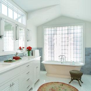 Maritim inredning av ett stort vit vitt en-suite badrum, med luckor med lamellpanel, vita skåp, ett fristående badkar, en dusch i en alkov, blå kakel, marmorkakel, blå väggar, marmorgolv, ett undermonterad handfat, marmorbänkskiva, vitt golv och dusch med gångjärnsdörr