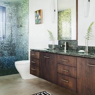 Diseño de cuarto de baño con ducha, actual, con lavabo integrado, armarios con paneles lisos, puertas de armario de madera en tonos medios, ducha empotrada, sanitario de una pieza, baldosas y/o azulejos multicolor, baldosas y/o azulejos en mosaico, paredes blancas y suelo de cemento