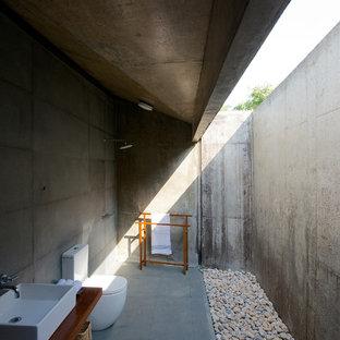 Inredning av ett modernt mellanstort brun brunt badrum, med träbänkskiva, en toalettstol med hel cisternkåpa, grå kakel, cementkakel, ett fristående handfat och en kantlös dusch