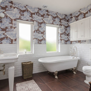 Photo of a classic ensuite bathroom in Belfast with a claw-foot bath, a two-piece toilet, white tiles, metro tiles, multi-coloured walls, a console sink and brown floors.