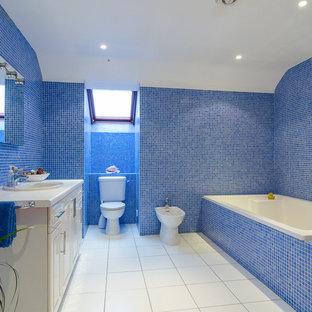 Modernes Badezimmer mit profilierten Schrankfronten, weißen Schränken, Einbaubadewanne, Bidet, blauen Fliesen, Mosaikfliesen und blauer Wandfarbe in Belfast