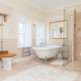 Medium sized country bathroom in Belfast with a claw-foot bath, a walk-in shower, a two-piece toilet, an open shower, beige tiles, beige walls and beige floors.