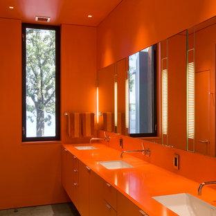 Exemple d'une salle de bain moderne avec un lavabo encastré, un placard à porte plane, des portes de placard oranges, un mur orange et un plan de toilette orange.