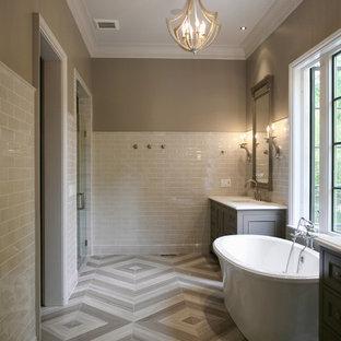 Imagen de cuarto de baño principal, actual, grande, con bañera exenta, paredes beige, armarios con paneles empotrados, puertas de armario grises, lavabo bajoencimera, encimera de mármol, baldosas y/o azulejos grises, baldosas y/o azulejos de piedra y suelo de piedra caliza