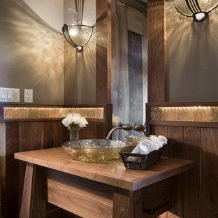 Foto di una stanza da bagno rustica con lavabo a bacinella, ante in legno bruno, top in legno e pareti grigie