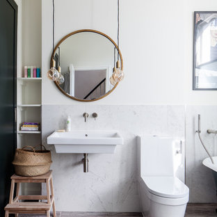 Classic shower room in London with a claw-foot bath, a shower/bath combination, a one-piece toilet, white tiles, marble tiles, white walls, a wall-mounted sink and brown floors.