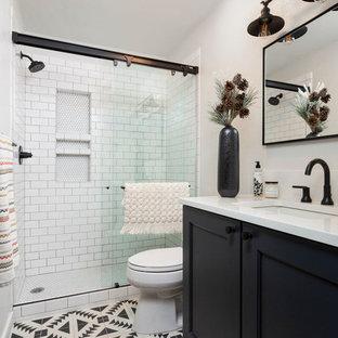 Esempio di una stanza da bagno con doccia classica con ante con riquadro incassato, ante nere, doccia alcova, piastrelle bianche, pareti bianche, lavabo sottopiano, pavimento multicolore, porta doccia scorrevole e top bianco