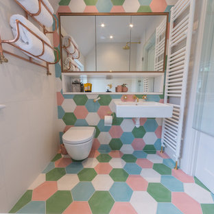 Idéer för eklektiska badrum med dusch, med våtrum, en vägghängd toalettstol, blå kakel, grön kakel, rosa kakel, vit kakel, cementkakel, grå väggar, cementgolv, ett väggmonterat handfat och flerfärgat golv