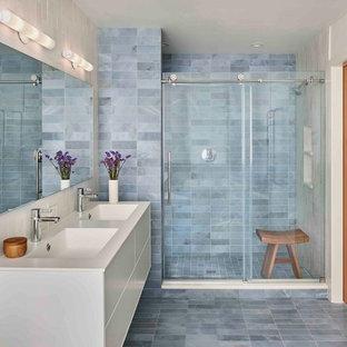 Idee per una stanza da bagno padronale design di medie dimensioni con ante lisce, ante bianche, doccia doppia, WC monopezzo, piastrelle blu, piastrelle di marmo, pareti blu, pavimento in marmo, lavabo integrato, top in superficie solida, pavimento blu e porta doccia scorrevole