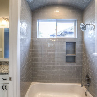 This is an example of a mid-sized arts and crafts master bathroom in Houston with shaker cabinets, white cabinets, an alcove tub, a shower/bathtub combo, a two-piece toilet, gray tile, glass tile, grey walls, an undermount sink and granite benchtops.