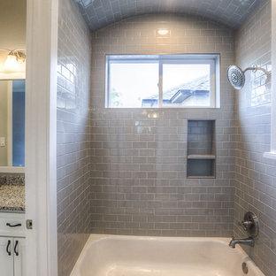 Foto di una stanza da bagno padronale stile americano di medie dimensioni con ante in stile shaker, ante bianche, vasca ad alcova, vasca/doccia, WC a due pezzi, piastrelle grigie, piastrelle di vetro, pareti grigie, lavabo sottopiano e top in granito