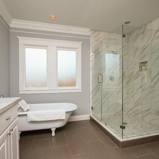 Неиссякаемый источник вдохновения для домашнего уюта: большая главная ванная комната в классическом стиле с белыми фасадами, ванной на ножках, угловым душем, белой плиткой, врезной раковиной, фасадами с выступающей филенкой, керамогранитной плиткой, серыми стенами, полом из керамогранита, столешницей из гранита и душем с распашными дверями
