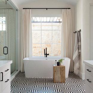 Inspiration för medelhavsstil vitt en-suite badrum, med släta luckor, vita skåp, ett fristående badkar, flerfärgat golv och dusch med gångjärnsdörr