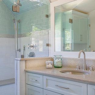 Cette image montre une petit salle de bain design avec des portes de placard blanches, un mur blanc, sol en stratifié, un lavabo encastré, un plan de toilette en quartz modifié, un sol marron, une cabine de douche à porte battante, un plan de toilette beige, un placard à porte shaker, un carrelage vert et un carrelage métro.
